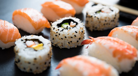 Close up of sushi served on black plate. Delicious japanese cuisine sushi prepared for one person. Fresh sushi served to eat at restaurant.