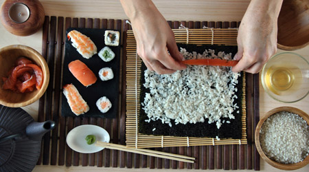 hands cooking sushi with rice, salmon and nori
